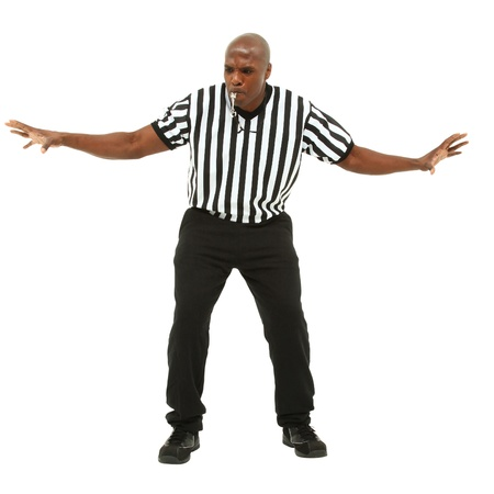 Attractive fit black man in referee uniform facing front and blowing whistle
