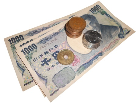 Japanese currency bills and coins stacked over white with clipping path.