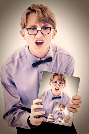 geeky: Adorable geeky teen boy holding electric notepad with photo of self. Stock Photo