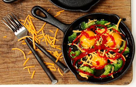meatless: Uncooked Raw Eggs in Skillet with Brocolli, Cheese and Sriracha Sauce ready to put in oven.