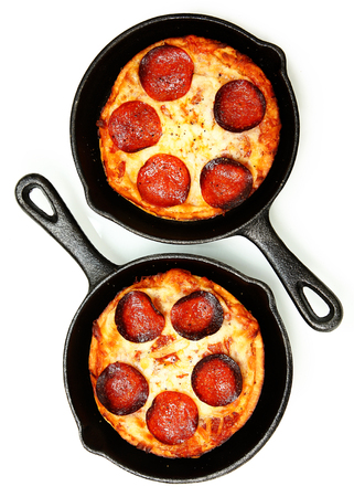 Two Single Serve Skillet Peperonni Pizzas Over White photo