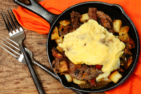 scrambled eggs: Texas Skillet Breakfast with Steak, Potato and Egg on Table