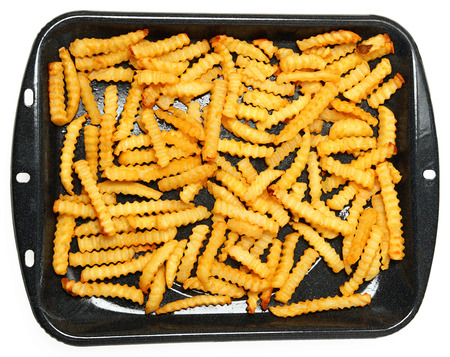 Homemade Oven Baked Crinkle Fries in Broiler Pan over White. photo
