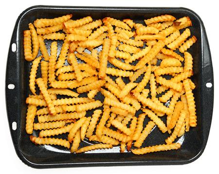 crinkle: Homemade Oven Baked Crinkle Fries in Broiler Pan over White.
