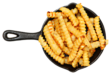 Oven Baked Crinkle Fries in Cast Iron Skillet over white. photo