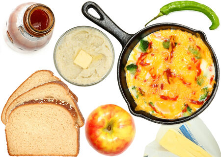 Breakfast over white, omelet, apple, egg, butter, bread, hot sauce, pepper. Imagens