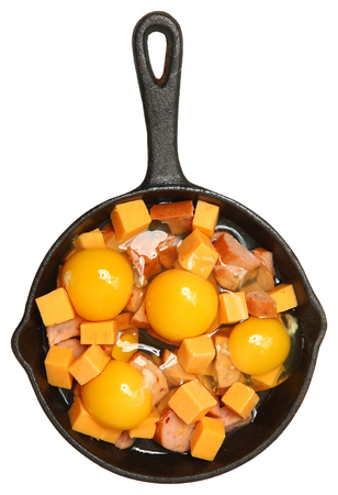 Raw Eggs, Cheese and Sausage in Cast Iron Skillet Isolated Over White. Standard-Bild