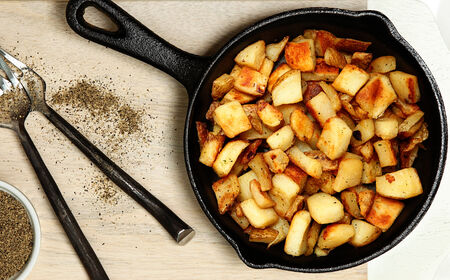 black pepper: Ranch Potatoes in Cast Iron Skillet on Cutting Board with Black Pepper.