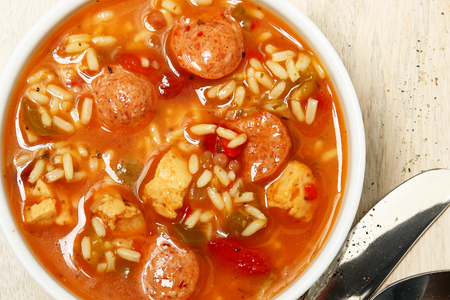 Bowl of Cajun Spicy Chicken and Sausage Gumbo Soup at Table photo