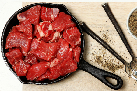 Raw Cubed Beef in Cast Iron Skillet on Table Top View. photo