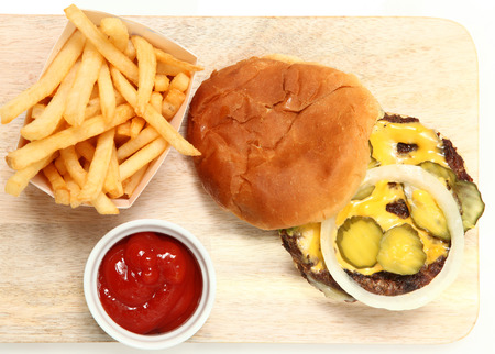 table top: Top View Burger and Fries Served on Cutting Board with Ketchup.
