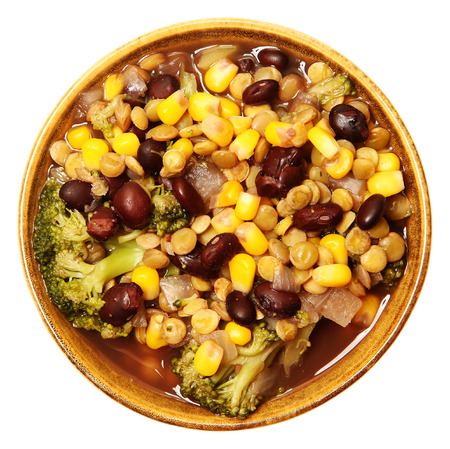 Vegan lentil soup and veggies in bowl with black beans, broccoli, onion, corn over white. Top view. Imagens