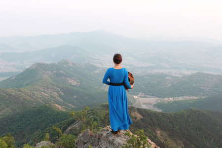 backview: blue dress woman standing at the top of mountain