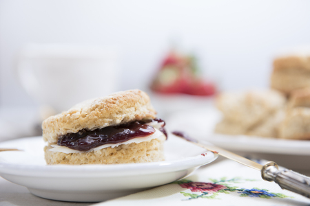 Traditional homemade british scones with butter and strawberry jam on white wooden table. Horizontal. Copy space.
