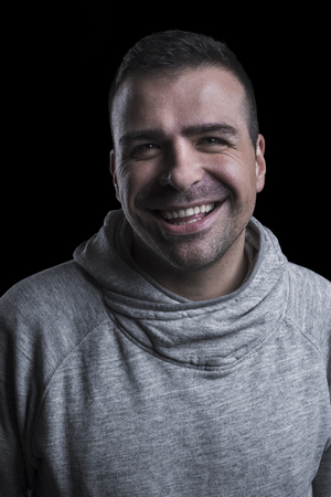 Studio portrait of a smiling man looking at the camera. Isolated on black background. Vertical.