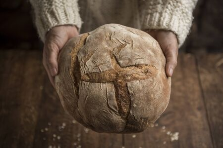 Bread, woman hands holding freshly baked sourdough bread on rustic background. Horizontal with Copy Space