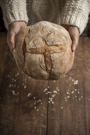 Bread, woman hands holding freshly baked country loaf on rustic background, with copy space