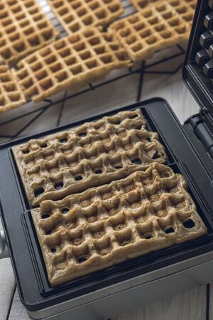 Homemade freshly baked waffles in iron waffle maker over a white rustic wooden table. 免版税图像