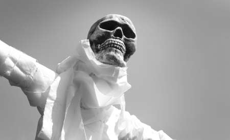 A gruesome scarecrow, comprising of bandages and skull stares upwards with unseeing eye sockets.
