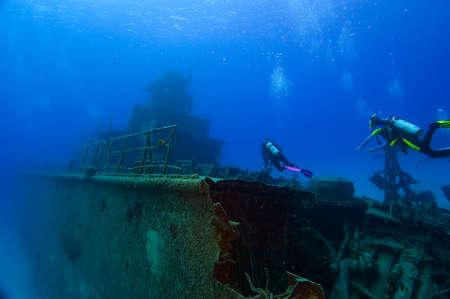 dive: Dos buceadores nadan hacia la superestructura de un naufragio. Enredado en los restos de los conocimientos adquiridos; el buque retrocede en el oc�ano azul en el fondo. Foto de archivo