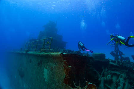 Two divers are swimming towards the superstructure of a shipwreck. Tangled wreckage in the foreground; the vessel recedes into the ocean blue in the background.