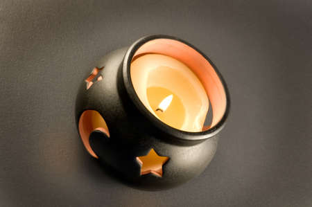 Looking down into a dark china cauldron filled with burning glowing candle, the molten wax can be seen.  The cutouts of stars and moon against a dark textured background  give a radiant glow and spooky feel.