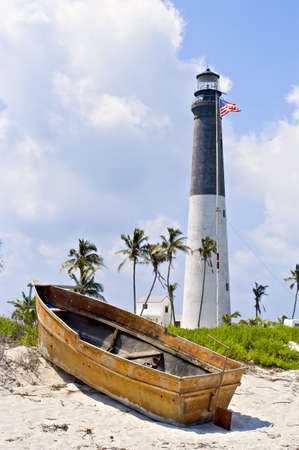 dry tortugas: A small boat has been washed up onto the shore near to the historic Loggerhead Key lighthouse [1858] on the Dry Tortugas. Stock Photo