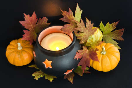 A candle in a cauldron with maple leaves and pumpkins. The reflected light from the flame casts an orange spooky glow on the background.