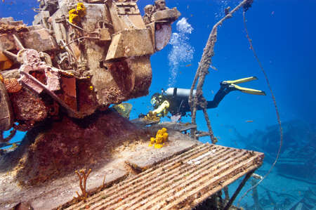 superstructure: A female diver is exploring the superstructure of the sunken wreck, the Tibbetts, a Russian frigate that was sunk in the waters off Cayman Brac.