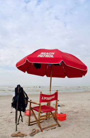 Lifeguard station with red umbrella and chair