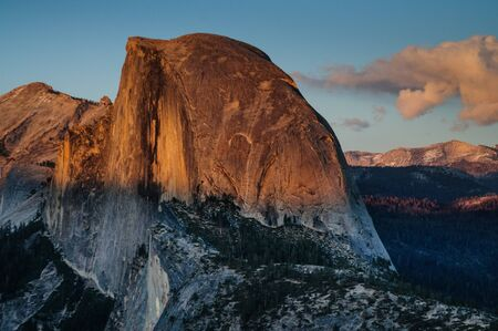 The setting sun illuminates Half dome, as seen from Glacier Point. Yosemite National Park, California, USA. Stock Photo
