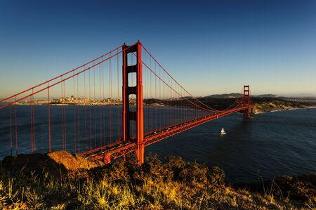 A little boat sails underneath the Golden Gate Bridge, San Francsico, during sunet.