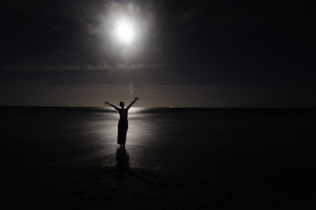 Young Woman Dancing in the Moonlight on Cocoa Beach, Florida, USA