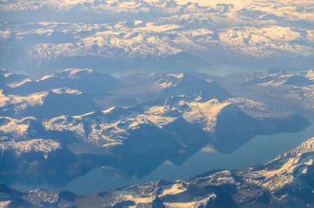 Mountains reflecting in frozen lakes near the coast of Greenland. Stock Photo
