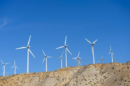A large group of wind turbines standing along the twentynine palms highway in Southern California, near North Palm Springs