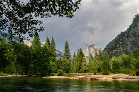 A rare July Thunderstorm building up over the Sierra Nevada Mountain range, seen here across the Merced river and Half dome, in Yosemite National Park.