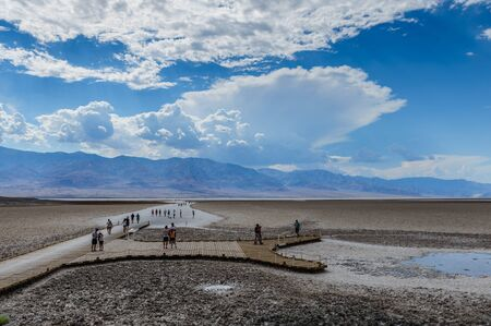 A scattered group of tourists walking down the salt flats near the Badwater area in Death Valley National Park, USA. Stock Photo