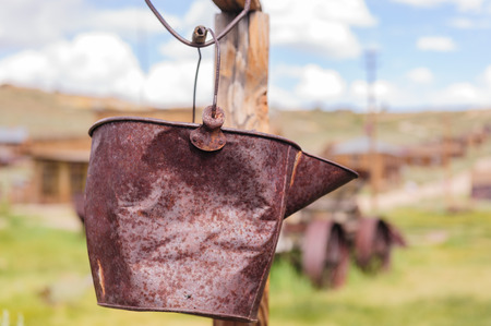 An old rusty bucket hanging from a wire in the Californian Ghost Town of Bodie on an early August summers day.