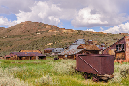 An old rusty iron cart is left in the Californian Ghost town of Bodie, on a summer day in early August. Stock Photo