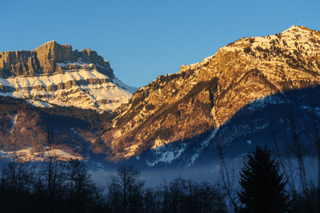 Low sun illuminatating the mountains near the  town of Chamonix-de-Mont Blanc on an early winters afternoon.