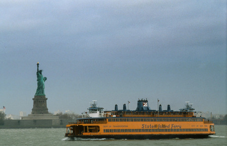 NEW YORK CITY, MARCH 2003. The Staten Island Ferry Passing in front of the Statue of Liberty in New York City. This Ferry is a popular among tourists for its scenic routes.