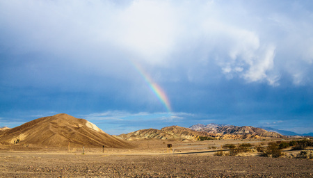A rare sighting of a rainbow over the Furnace Creek Campground on a summer evening in Death Valley. Stock Photo