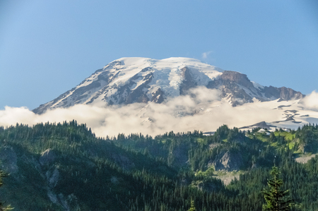 Mount Rainier peaking through the clouds and the surrounding forest. Stock Photo - 104592128