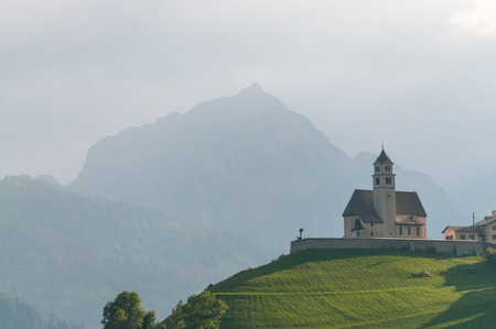 The Church in the village of Colle Santa Lucia in the Golden hours, just before sunset. Italian Dolomites on a summers evening. Stock Photo