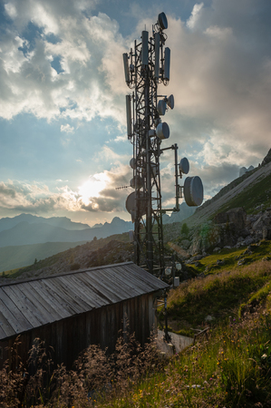 A radio mast at the Passo Gi Giao, in the italian Dolomites during sunset.