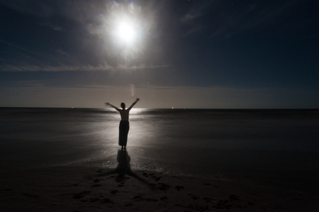Silhoutte of a young woman dancing on the beach at Cocoa, Florida, expression joy, happiness, and freedom.