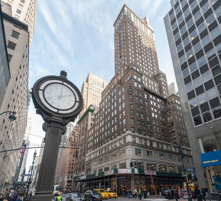 New York, USA, December 21, 2015. A street Clock on fifth Avenue, higlighting the busy street traffic of central manhatten in this wide-angle shot. 版權商用圖片 - 138205253