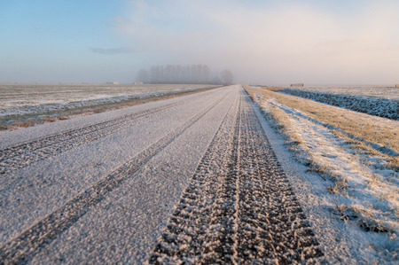 Tyre tracks making a fresh impression on a straight country road. Image from a relatively rare white Christmas in the Dutch Province of Friesland.