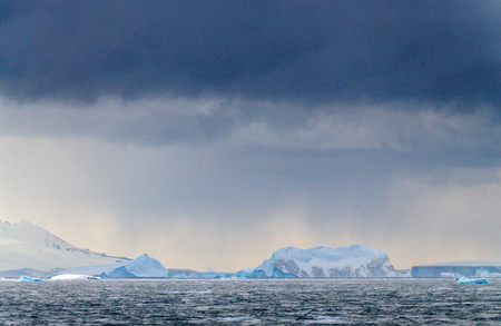 Giant icebergs floating off the Coast of Brown Bluff, the Northernmost tip of the Antarctic Peninsula. Storm Clouds are lining the Skies.