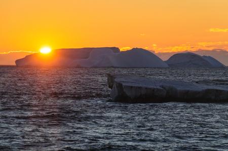 Antarktischer Sonnenuntergang: Schwimmende Eisberge im Weddellmeer, nahe der Antarktischen Halbinsel, von einem antarktischen Erkundungsschiff aus gesehen